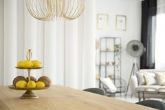 Citruses in dining room. Citruses on wooden table under gold lamp in dining room interior Royalty Free Stock Photography