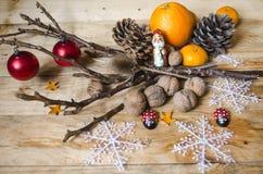 Citrusfrukter, choklad, muttrar med kottar och leksaker på bräden Arkivbild