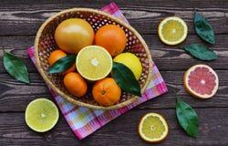 Citrusfrukter i en korg ligger på en trätabell arkivfoto