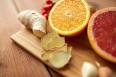Citrusfrukter, ingefära och vitlök på trä Royaltyfri Bild