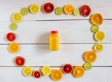 Citrusfrukter och fruktsaft på vit träbakgrund arkivfoto