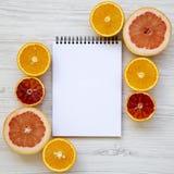 Citrusfrukter sicilian apelsin, grapefrukt, apelsin med notepaden på en vit träyttersida, över huvudet sikt Lekmanna- lägenhet To royaltyfria foton