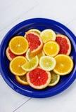 Citrusfruktskivor i en blå keramisk platta Arkivbild