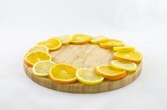 Citrusskivor på träbrädet som isoleras på vit Fotografering för Bildbyråer
