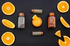 Citrusvruchten oranje schoonheidsmiddel voor natuurlijk kuuroordbad op zwart lijst achtergrond hoogste meningspatroon stock foto