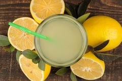 Citrusvruchtensappen citroensap in een glas met verse citroenen op een bruine houten lijst Mening van hierboven stock foto's