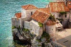 Città antica con i tetti rossi che stanno sull'alta scogliera alla spiaggia Immagini Stock
