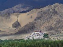 Città buddista del monastero di Tiksi contro il contesto delle montagne enormi dei colori marroni e beige, nella priorità alta un Fotografia Stock