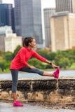Città che esegue la donna in buona salute del corridore di stile di vita che allunga esercizio di gambe per funzionare nel fondo  immagini stock