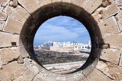 Città costiera Essaouira attraverso un foro del bastione. Fotografie Stock Libere da Diritti