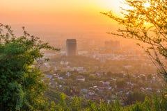 Città di Almaty nella nebbia nel tramonto con smog e polvere nell'aria, il Kazakistan Fotografia Stock Libera da Diritti
