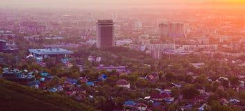 Città di Almaty nella nebbia nel tramonto con smog e polvere nell'aria, il Kazakistan Fotografia Stock