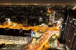 Città di Bangkok con il semaforo ed alta costruzione alla notte Fotografia Stock