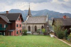 Città di Grundlsee con la vecchia chiesa di parrocchia un giorno nuvoloso di autunno La Stiria, Austria fotografia stock libera da diritti