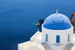 Città di OIA sull'isola di Santorini, Grecia Chiesa bianca con la cupola blu Fotografie Stock Libere da Diritti