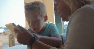 In città di Perea, la Grecia si siede una nonna con il suo nipote e gli insegna come compressa di uso video d archivio