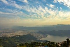 Città di Pokhara sotto un cielo blu con le nuvole bianche in una valle della montagna nebbiosa alla vista aerea di Phewa del lago immagine stock