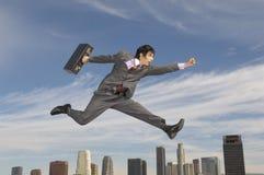 Città di Running Midair Above dell'uomo d'affari immagini stock