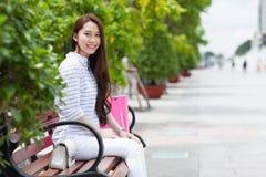 Città di seduta di estate del banco di sorriso asiatico della donna Fotografia Stock Libera da Diritti
