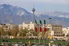 Città di Teheran con le bandiere dell'Iran e di Milad Tower nel telaio Fotografie Stock Libere da Diritti
