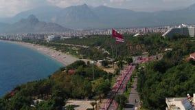 Città e spiaggia di Adalia con la vista aerea delle bandiere di Adalia e della Turchia stock footage