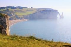 Città francese di Etretat sulla riva dell'oceano su un sole luminoso Immagine Stock