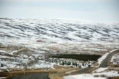 Città fuori città, montagna della neve, strada asfaltata, Islanda Fotografie Stock