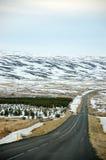 Città fuori città, montagna della neve, strada asfaltata, Islanda Immagine Stock
