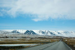Città fuori città, montagna della neve, strada asfaltata, Islanda Immagini Stock Libere da Diritti