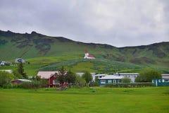 Città islandese Vik con la sua chiesa famosa sulla collina e una cittadina come simbolo delle città tranquille in Islanda Fotografia Stock Libera da Diritti