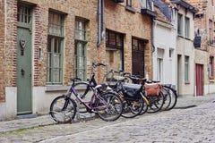 Città medievale tradizionale Via pavimentata stretta con le vecchie case con mattoni a vista e bici vicino all'entrata fotografia stock