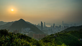Città moderna accanto alla montagna nel tramonto Fotografia Stock