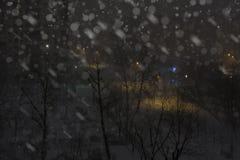 Città nevosa di notte con le costruzioni e l'iluminazione pubblica Città di inverno fotografia stock libera da diritti