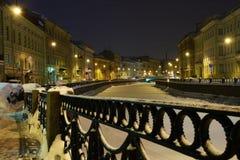 Città romantica di inverno di notte con neve e un fiume congelato Fotografie Stock