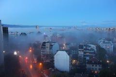 Città sotto la nebbia di mattina fotografia stock libera da diritti