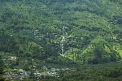 Città sul pendio di una montagna verde con una cascata fotografia stock