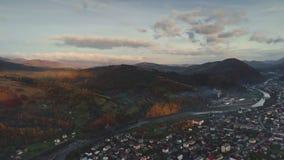 Città sulla sponda del fiume d'avvolgimento della montagna e sulle foreste verdi stock footage