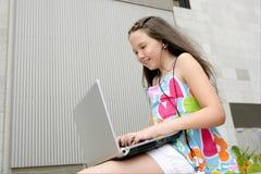 Città teenager del computer portatile della bambina del bello brunette Fotografia Stock