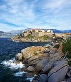 Cittadella di Calvi veduta dalle rocce della costa della penisola di Revellata Immagine Stock