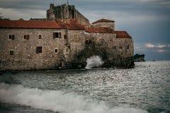 Cittadella di pietra sull'alta scogliera al sera tardi in mare tempestoso Immagini Stock Libere da Diritti