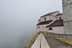 Cittadina italiana in alta montagna nelle nuvole e nella nebbia Fotografia Stock