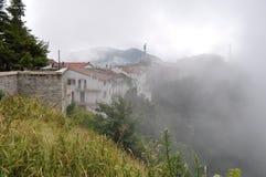 Cittadina italiana in alta montagna nelle nuvole e nella nebbia Fotografia Stock Libera da Diritti