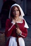 Cittadina in vestito rosso con un grembiule ed in chaperon sulla via immagini stock