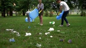 Cittadini attivi che raccolgono immondizia in parco pubblico, società contro inquinamento fotografia stock libera da diritti