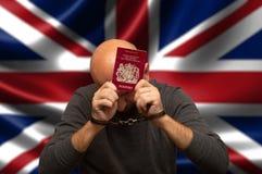 Cittadino detenuto dell'Inghilterra in manette con un passaporto in sue mani, nascondentesi fotografia stock libera da diritti