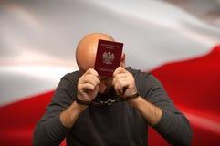 Cittadino polacco detenuto in manette con un passaporto in sue mani, nascondentesi fotografie stock