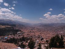 City and trees. Red tile roof, trees and city with distant mountains, sky with white clouds and black background, location near the city of Cusco stock images