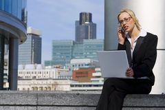 In The City. A beautiful young female executive talking on her cell phone and working on her laptop in a hi-tech urban surrounding Royalty Free Stock Photos