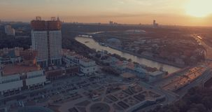 City Aerial View at Sunset. Aerial view of the Luzhnetsky metro bridge, passenger boat floating along the Moscow River, heavy traffic and building of Russian stock video footage