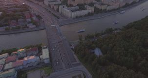 City Aerial View at Sunset. Aerial view of the Luzhnetsky metro bridge, passenger boat floating along the Moscow River, heavy traffic and building of Russian stock footage